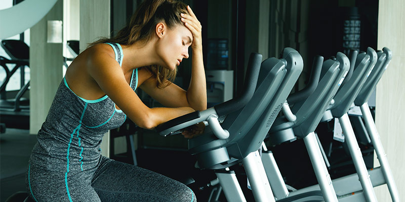 Exhausted woman on exercise bike