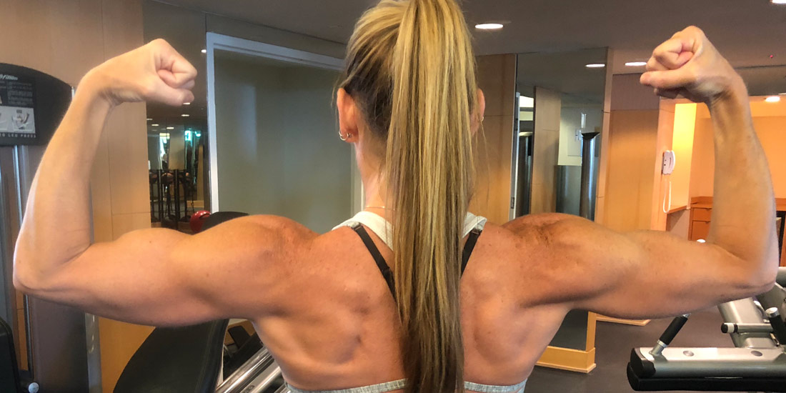 View of Melissa's shoulders and arms as she flexes her impressive muscles