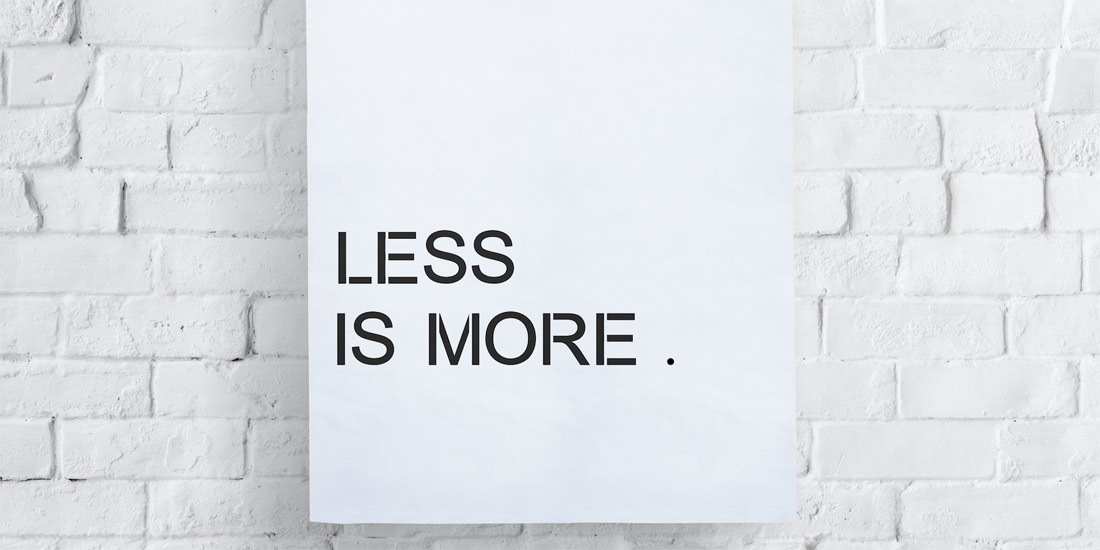 "White sign on white brick wall that says ""Less is More."""