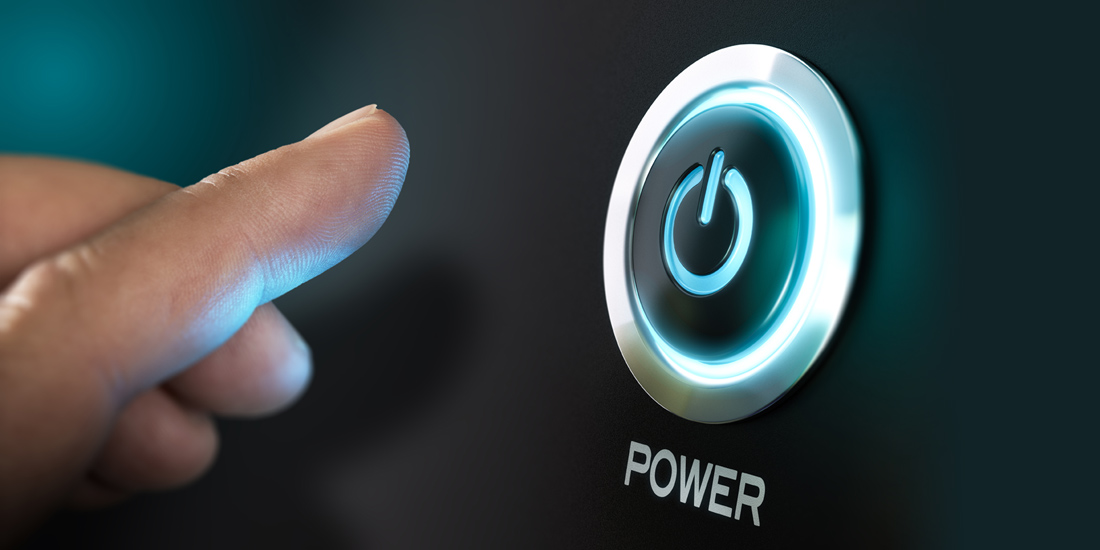 Finger pushing a high tech glowing power button